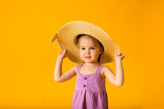 Portrait of a little girl in a sundress and a straw hat on a yellow surface with space for text