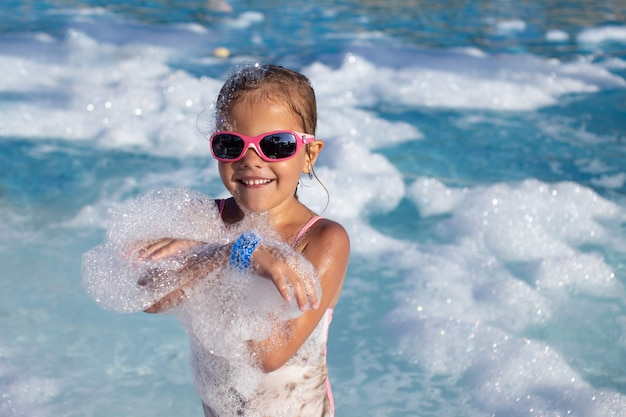Portrait of a little girl in sunglasses and a swimsuit in the water with foam