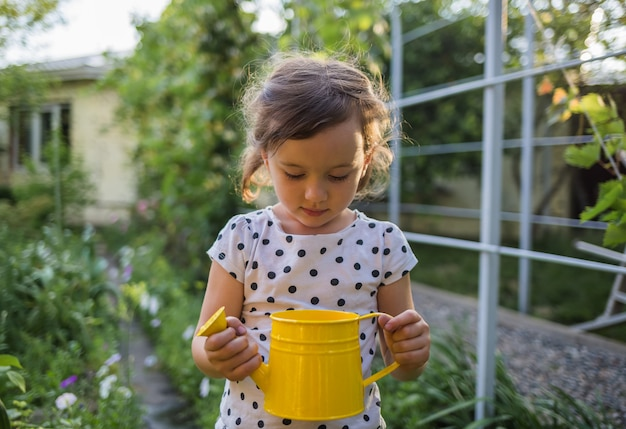 Portrait of a little girl at sunset standing in the garden in a yellow watering can