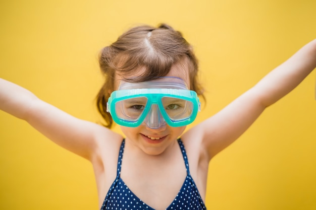 Portrait of a little girl in swimming glasses on a yellow isolated background with space for text
