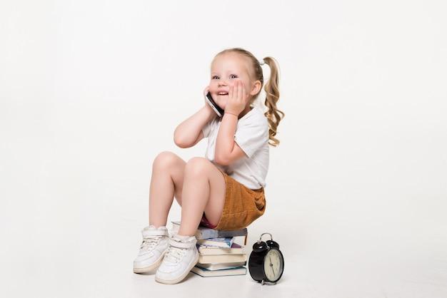 Ritratto di una bambina parla al telefono seduto su una pila di libri.