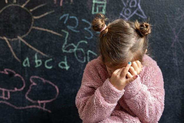 Портрет маленькой девочки расстроен, закрыла лицо