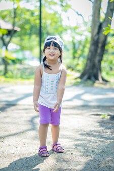 Portrait of little girl wear hat walking in the park