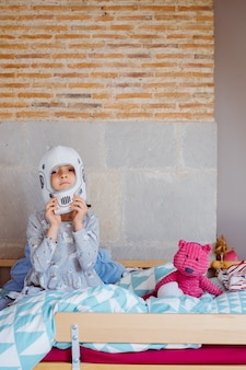 Portrait of a little girl wearing an astronaut helmet sit on the bed.