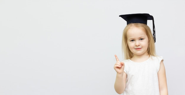 Portrait of little girl wearing graduate hat with copy space isolated on white background