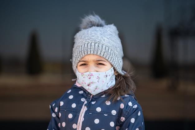 Ritratto di una bambina che indossa cappello e maschera durante la pandemia di coronavirus.
