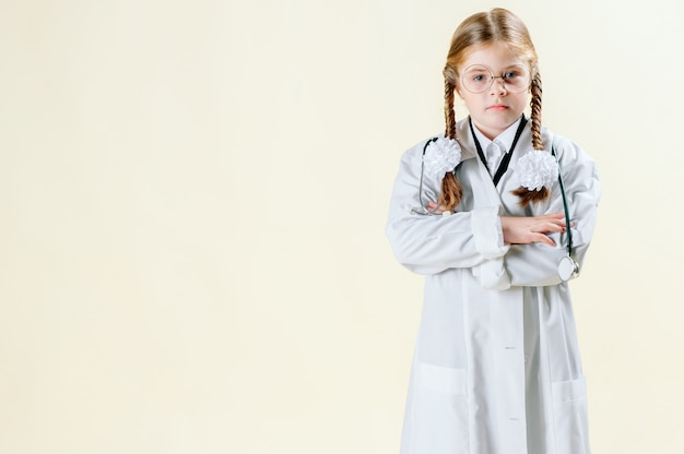 Portrait of a little girl in a white doctor s coat with glasses, documents and a stethoscope who looks at the camera and smiles