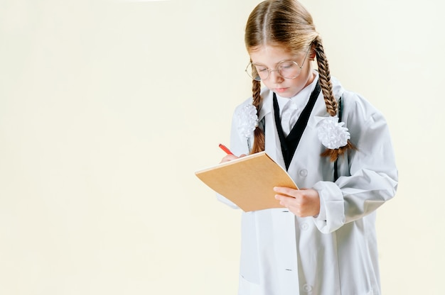 Portrait of a little girl in a white doctor s coat with glasses, documents and a stethoscope who looks at the camera and smiles.