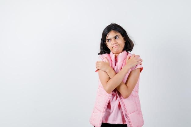 Ritratto di una bambina in maglietta bianca e giubbotto imbottito che si abbraccia Foto Gratuite