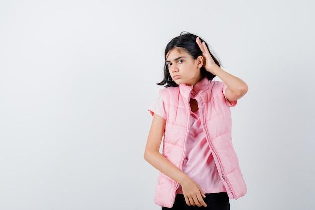 Ritratto di una bambina in maglietta bianca e giubbotto imbottito