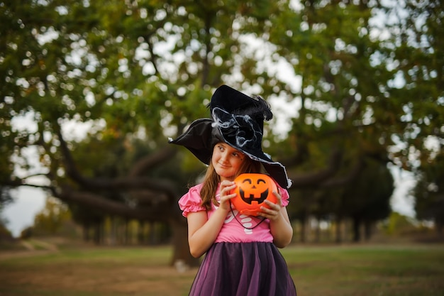Portrait of little girl in witch halloween costume and black hat