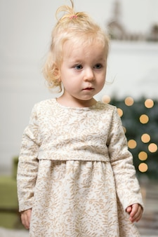 Portrait of a little girl with blonde hair in a photo of a christmas tree and new year's decor on the eve of christmas