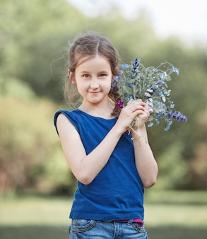 Portrait of a little girl with a bouquet of wild flowers.