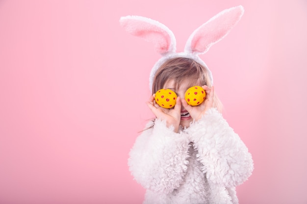 Portrait of a little girl with bunny ears and easter eggs