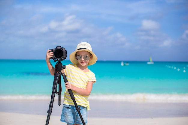 Portrait of little girl with camera on a tripod at white sandy beach