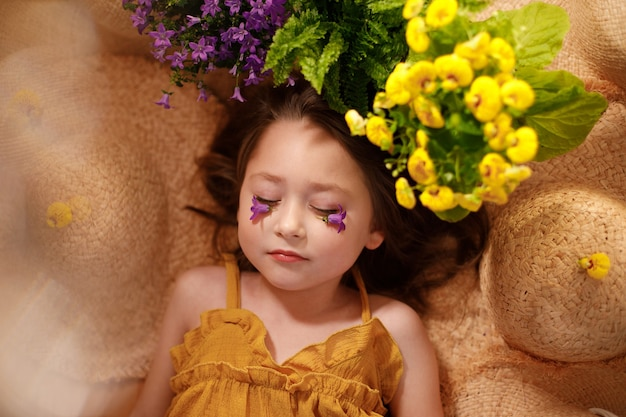 Portrait of a little girl with flowers on face lying from straw hats, summer and travel feeling concept