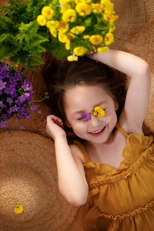 Portrait of a little girl with flowers on face lying from straw hats, summer and travel feeling concept.