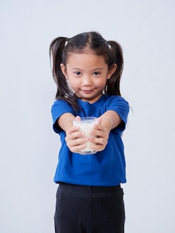 Portrait of little girl with glass of milk on light