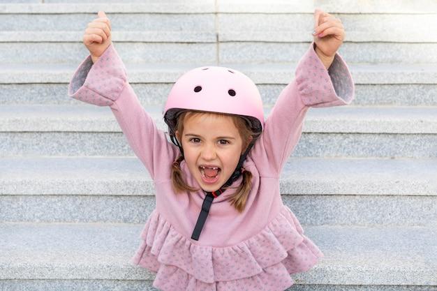 彼女の手を上げるヘルメットと肖像画の少女