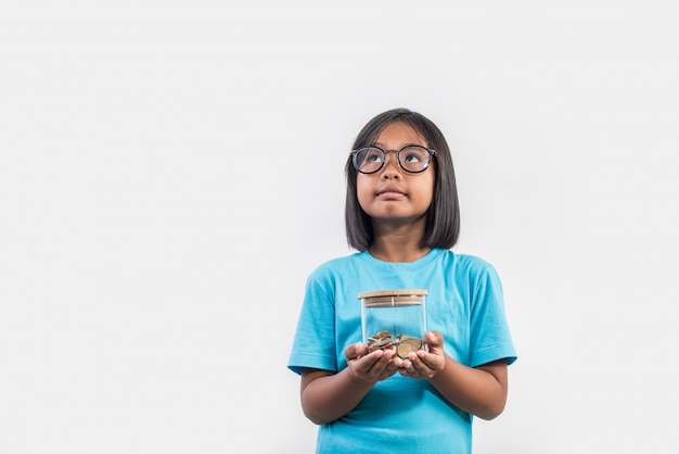 Portrait of little girl with her savings in studio shot