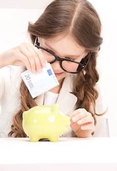 Portrait of little girl with piggy bank and money