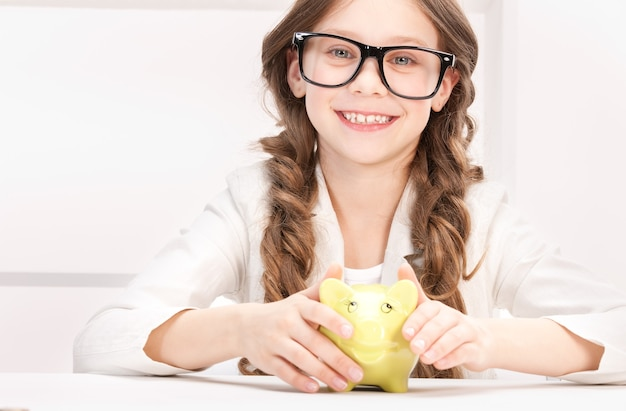 Portrait of little girl with piggy bank