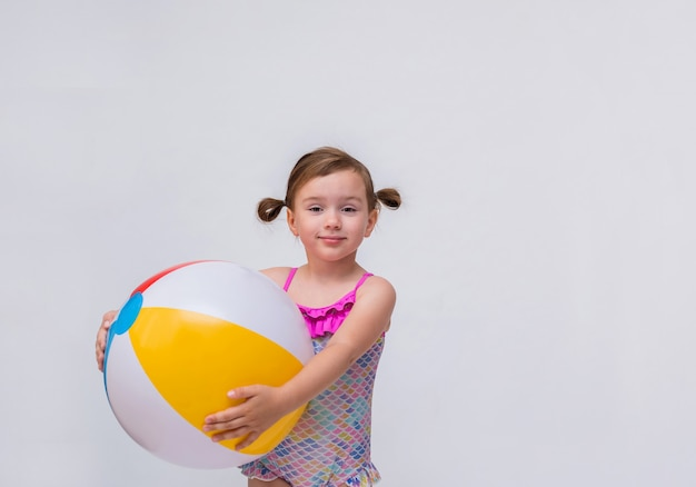 Portrait of a little girl with ponytails in a swimsuit with an inflatable ball on a white isolated