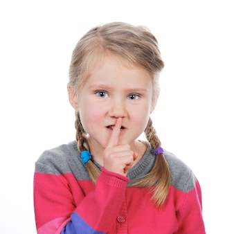 Portrait of little girl with silence gesture over white space