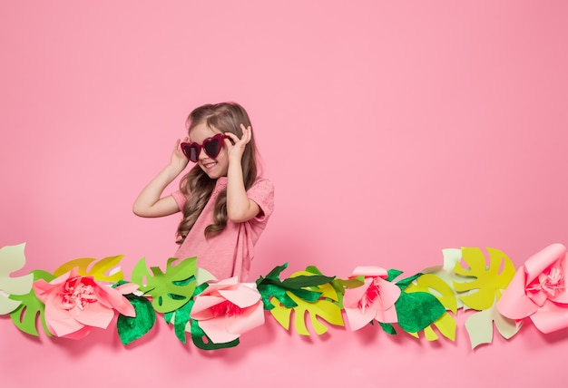 Portrait of a little girl with sunglasses on a pink background