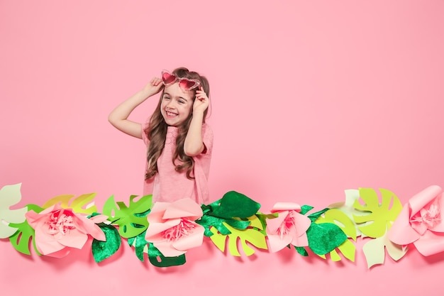 Portrait of a little girl with sunglasses on a pink wall