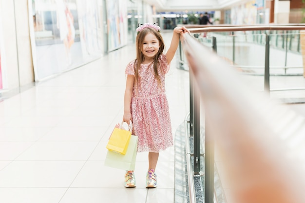 Portrait of a little happy girl in the mall. a smiling laughing girl in a pink dress with multi-colored bags in her hands is engaged in shopping.