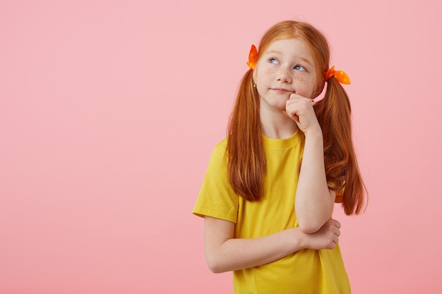 Portrait little pensive freckles red-haired girl with two tails, looks away, touches cheeks, wears in yellow t-shirt, stands over pink background.