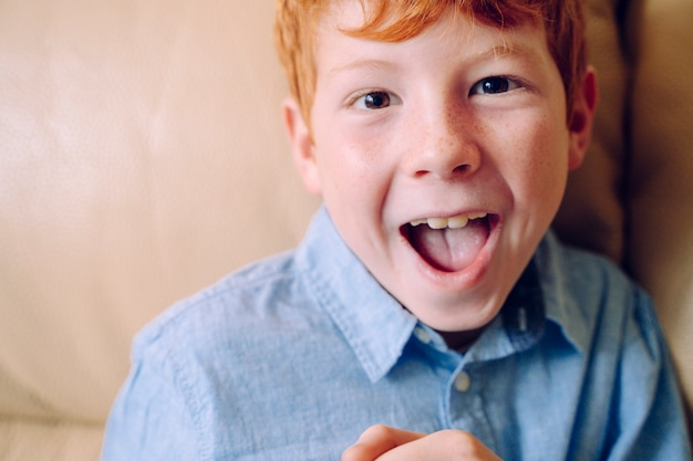 Portrait of a little red haired boy opening his mouth with expression of surprise.