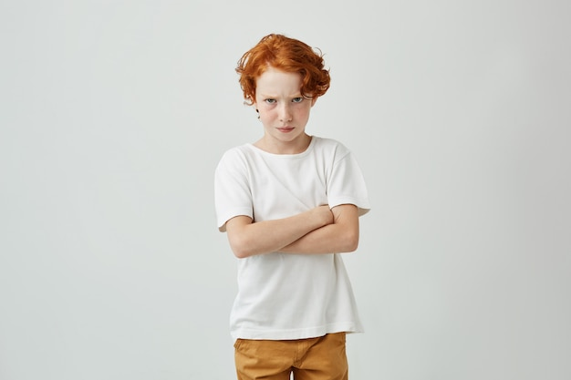 Portrait of little red haired boy with cute freckles in white tshirt looking with offended expression when his mom banned him to go outside