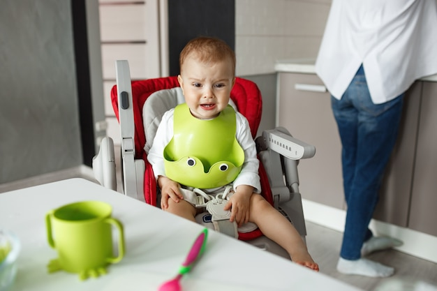 Portrait of little scared baby boy sitting in baby chair in kitchen, crying and screaming while mother cooking him food.