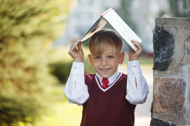 Portrait little schoolboy on nature background.