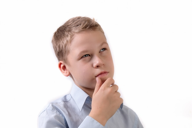 Portrait of a little schoolboy in a pensive pose isolated on white background