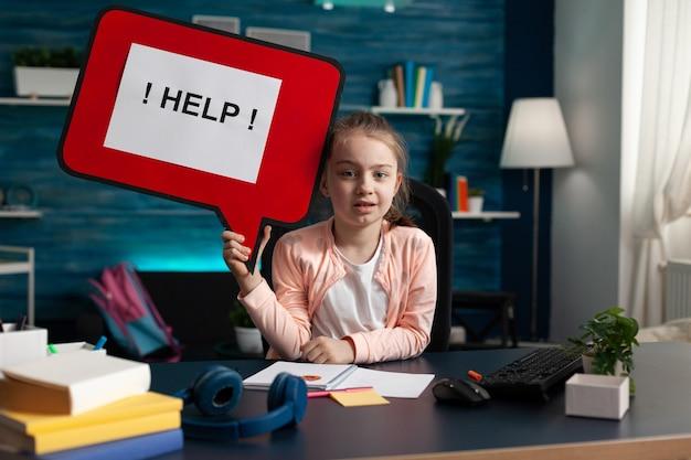 Ritratto di un piccolo scolaro che tiene in mano un banner di aiuto