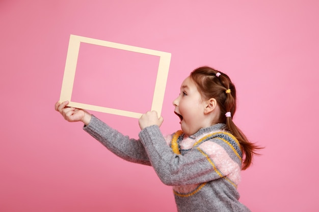 Portrait of a little screaming girl holding blank frame for mock-up on a pink background