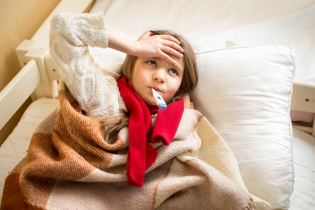 Portrait of little sick girl measuring temperature and holding hand on head