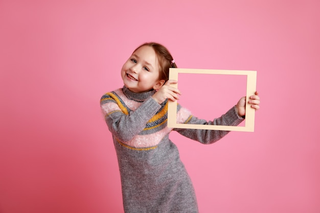 Portrait of a little smiling girl holding blank frame for mock-up on a pink background.