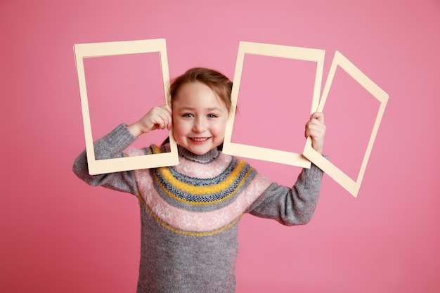 Portrait of a little smiling girl holding three blank frames for mock-up on a pink background