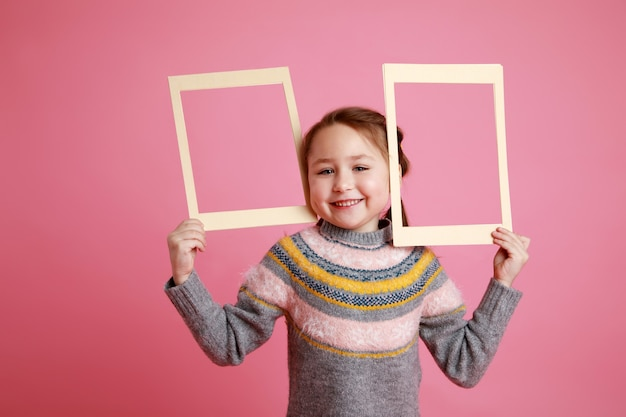 Portrait of a little smiling girl holding two blank frames for mock-up on a pink background