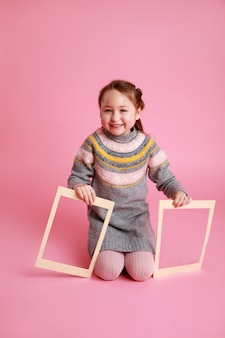 Portrait of a little smiling girl sitting and holding two blank frames for mock-up on a pink background
