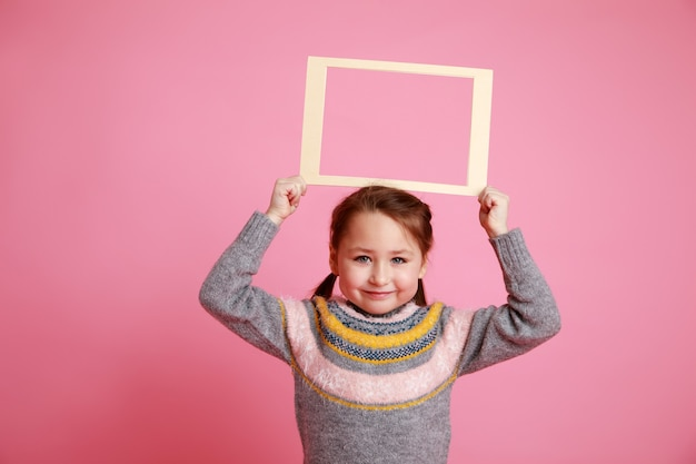 Portrait of a little smiling girl in warm dress holding blank frame for mock-up on a pink background