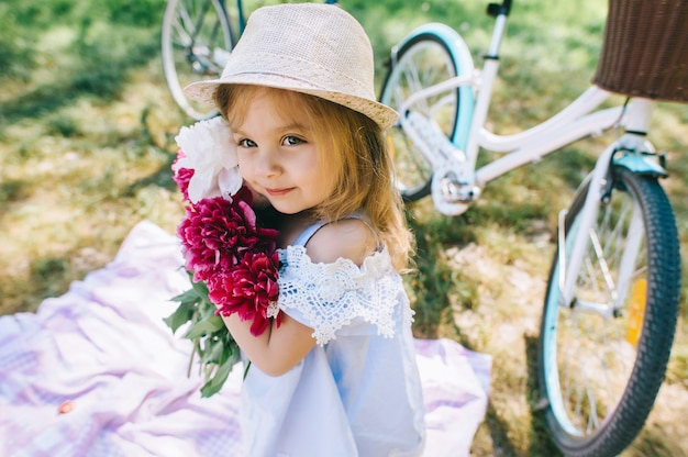 Portrait of a little smiling girl with big bouquet of flowers