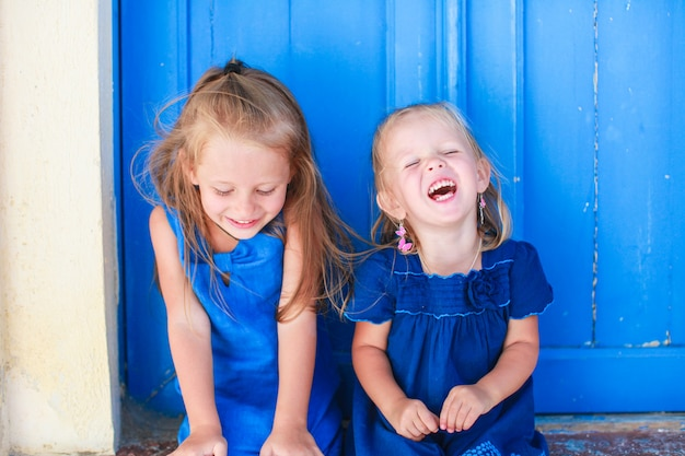 Portrait of little smiling girls sitting near old blue door in greek village, emporio, santorini