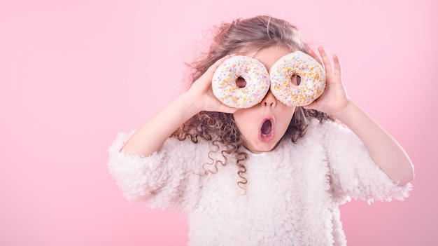 Portrait of a little surprised girl with donuts