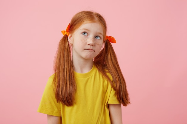 Portrait little thinking freckles red-haired girl with two tails, looks away, touches cheeks, wears in yellow t-shirt, stands over pink background with copy space.