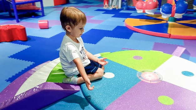Portrait of little toddler boy crawling and playing on the colorful children palyground covered with soft mats in shopping mall